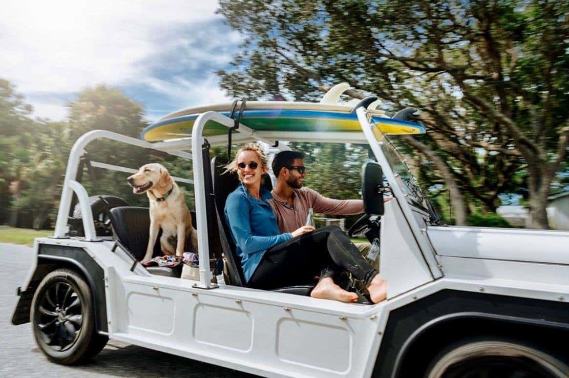 Couple and a dog riding in a Moke