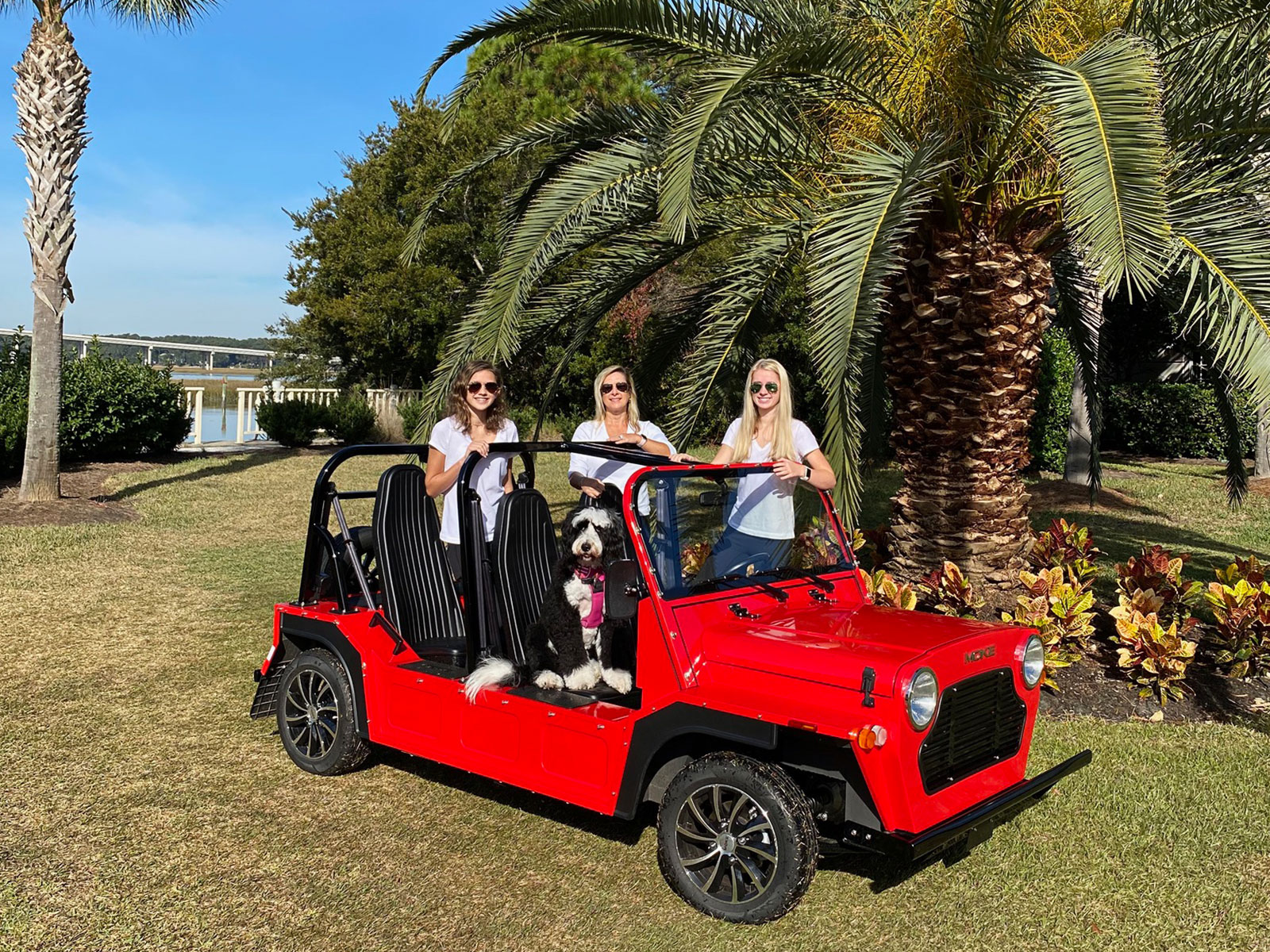 three women and a dog in a red Moke